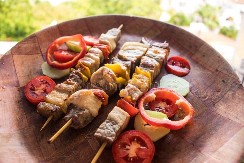 Carne Skewered preparada na grade com vegetais No espeto ou shashlik assado em varas foto de stock