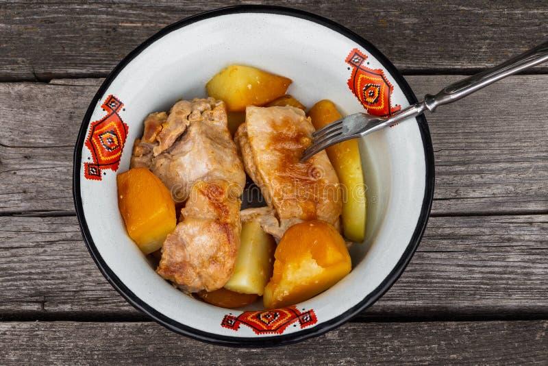 Carne succosa dell'arrosto con le patate servite in una ciotola del metallo bianco con un ornamento rosso con una forcella su un  fotografie stock libere da diritti