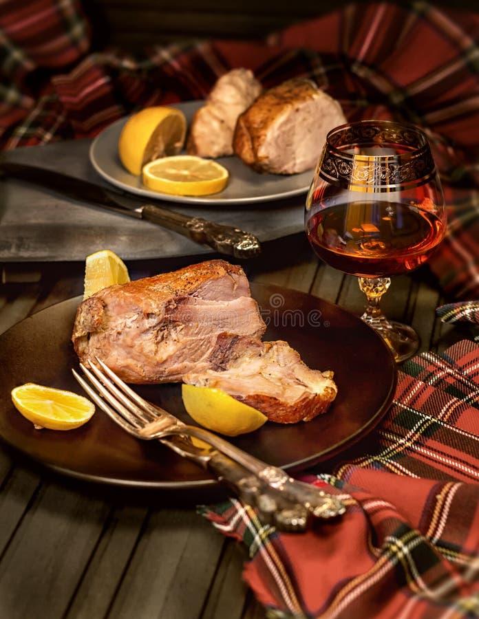 Carne suculenta em uma placa em um restaurante e em um vidro do conhaque imagem de stock