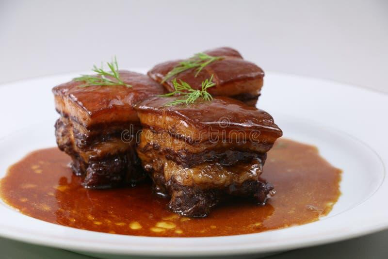 Carne suina brasata nello stile cinese con le erbe sul piatto bianco fotografia stock