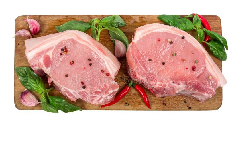 Carne suina cruda sul tagliere di legno con le erbe e le spezie isolate su fondo bianco Cottura del concetto immagini stock