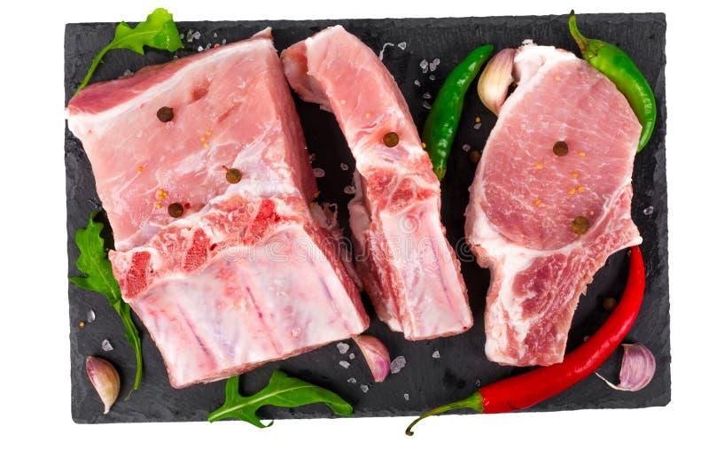 Carne suina cruda sulle ossa con peperoncino ed aglio su un'ardesia nera isolata su fondo bianco fotografia stock libera da diritti