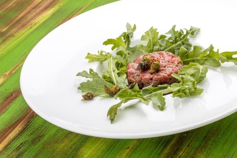 Carne tartare com alcaparras em uma tabela de madeira verde fotos de stock royalty free