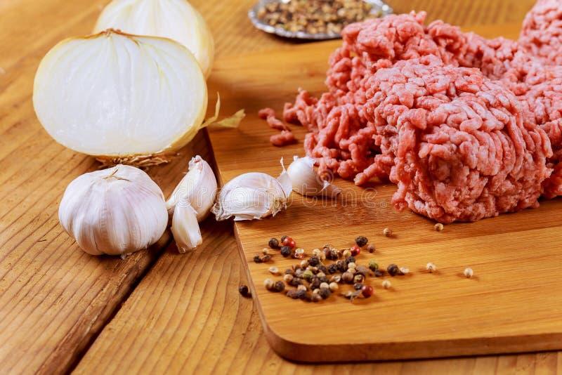 Carne tritata in carta di macellaio con l'aglio della cipolla immagine stock libera da diritti
