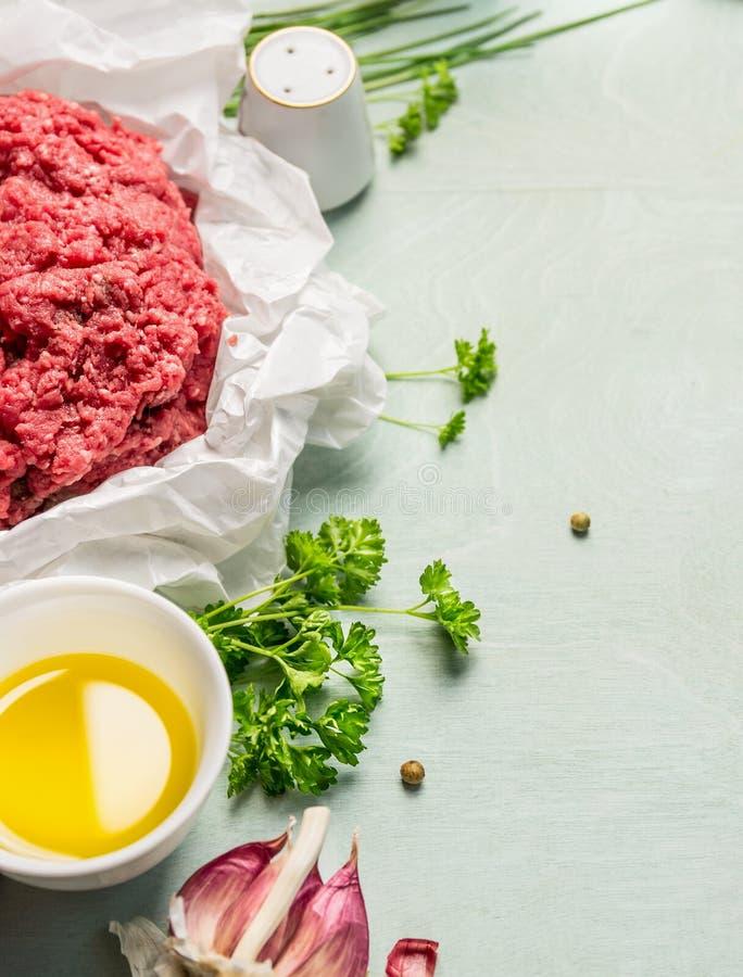 Carne tritata cruda in carta sgualcita con le erbe e l'olio freschi, preparazione su fondo di legno fotografia stock libera da diritti