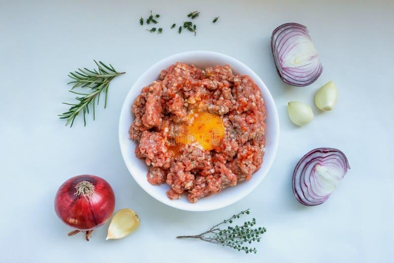Carne tritata cruda con pepe, l'uovo, le erbe e le spezie per la cottura delle cotolette, hamburger, polpette fotografie stock