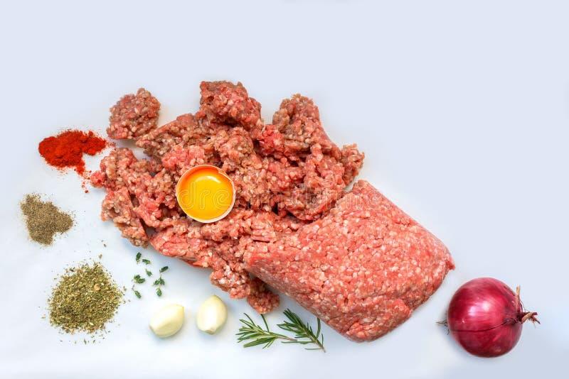 Carne tritata cruda con pepe, l'uovo, le erbe e le spezie per la cottura delle cotolette, hamburger, polpette immagini stock libere da diritti