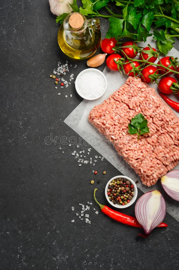 Carne tritata cruda su carta con gli ortaggi freschi e le spezie su fondo nero fotografie stock libere da diritti