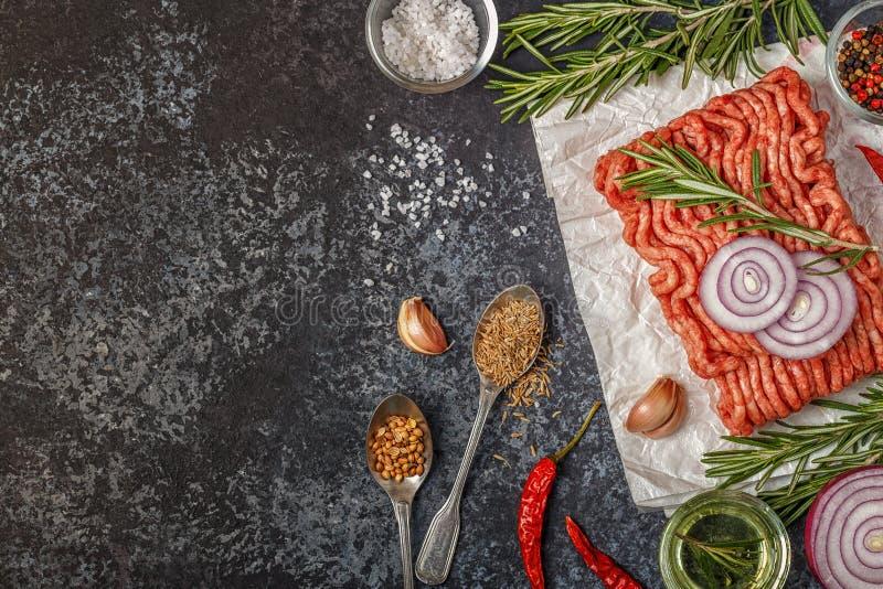 Carne tritata cruda su carta con la cipolla, le erbe ed i condimenti sul bla immagine stock