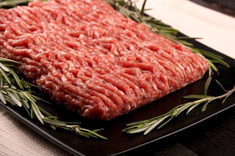 Carne tritata cruda su carta, sugli ingredienti per l'hamburger con il pomodoro, sul pepe, sulla cipolla, sulle spezie e sui cond immagini stock
