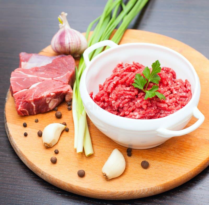 Carne tritata in una ciotola bianca con le erbe e le spezie fresche su un DES immagini stock