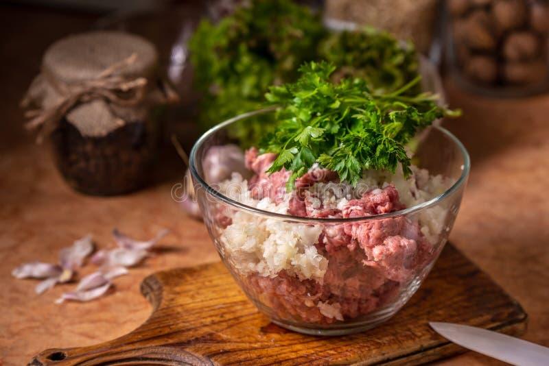 Carne triturada com cebola e salsa desbastadas em uma placa de vidro fotografia de stock