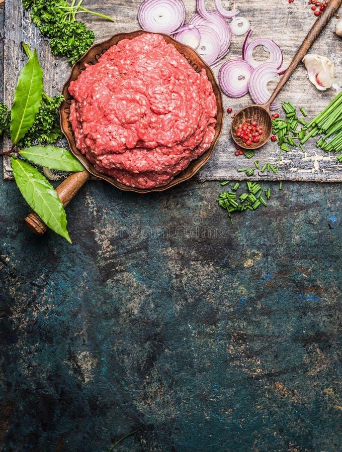 Carne triturada na frigideira com a colher de cozimento de madeira e tempero fresco no fundo rústico, vista superior foto de stock