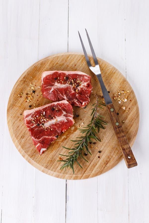 Carne vermelha e alecrins sobre o fundo branco foto de stock