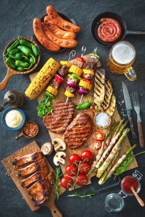 Carne y verduras asadas a la parrilla en la placa de piedra rústica imágenes de archivo libres de regalías