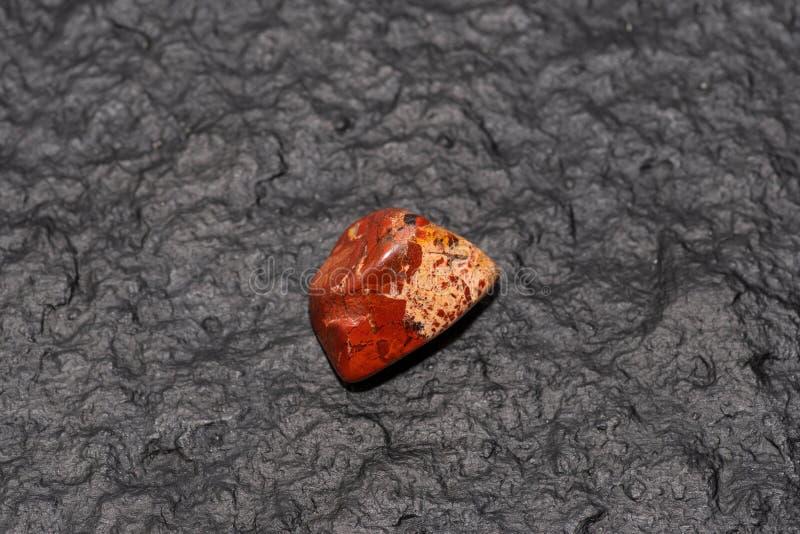 Carneol-Edelstein lokalisiert auf schwarzem Steinhintergrund Niedrige Schärfentiefe stockfotografie
