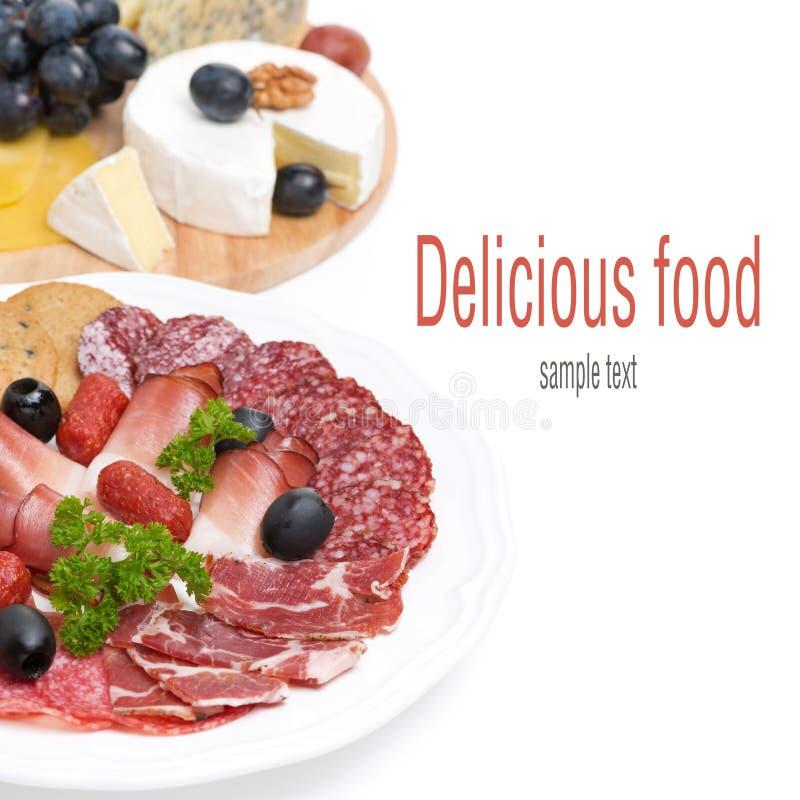 Carnes clasificadas de la tienda de delicatessen y una placa del queso y de las uvas, aislada imagen de archivo