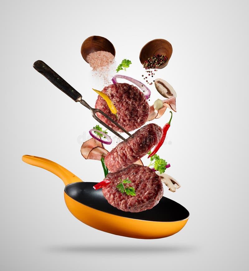 Carnes crudas de la hamburguesa que vuelan con los ingredientes libre illustration