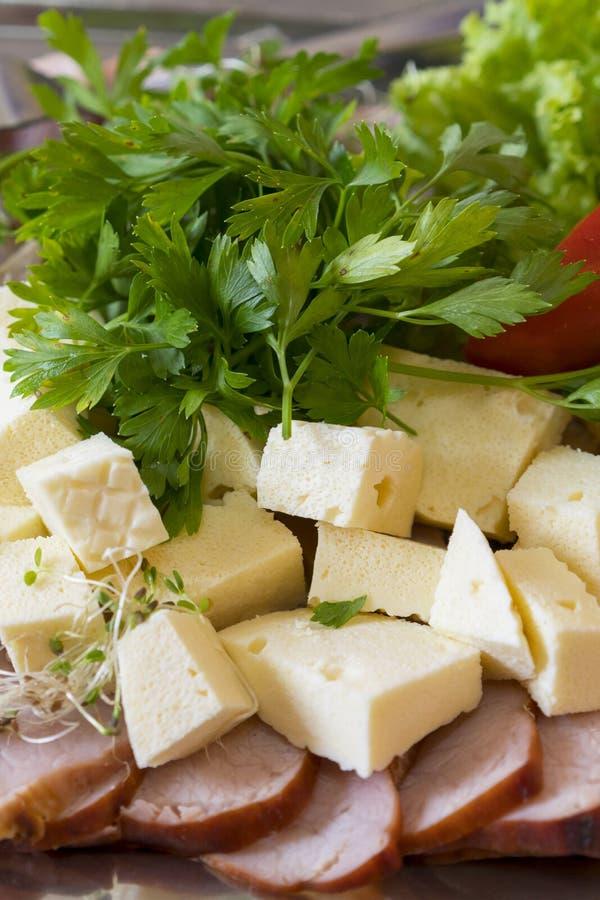 Carnes frias com queijo As fatias de queijo e de italiano do emmental cozeram o presunto Bandeja com bacon, cubos do queijo, sala imagem de stock