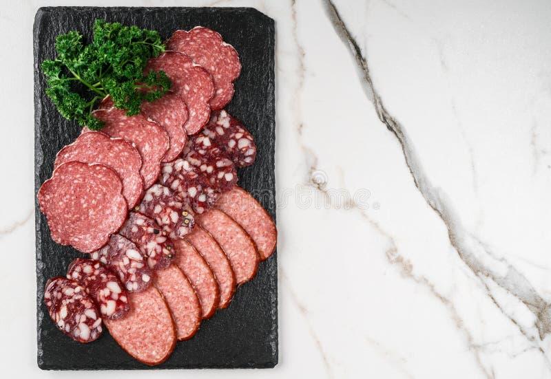 Carnes frias da bandeja do Antipasto com prosciutto, salsicha, salame na placa da pedra da ardósia sobre o fundo de mármore Aperi fotografia de stock