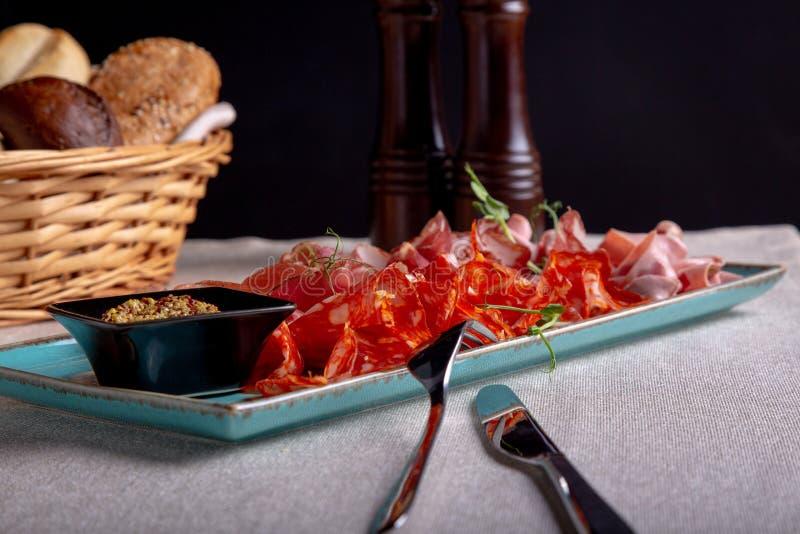 Carnes frias sortidos, prosciutto, presunto das fatias, carne de vaca seca, salame, carne e mostarda no fundo preto Aperitivo da  imagem de stock