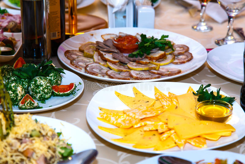Carnes y quesos en la tabla de banquete imagen de archivo
