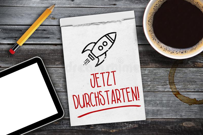 Carnet à dessins, comprimé, tasse de café sur un bureau en bois avec les mots allemands pour le début maintenant - le jetzt durch images libres de droits