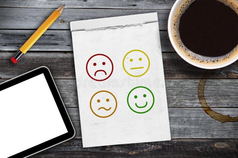 Carnet à dessins sur un bureau avec le service à la clientèle d'émoticônes d'estimation images libres de droits