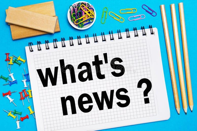 Carnet avec des notes quelles actualités du ` s avec le bureau usinent sur un fond bleu Concept quelles actualités du ` s photos stock