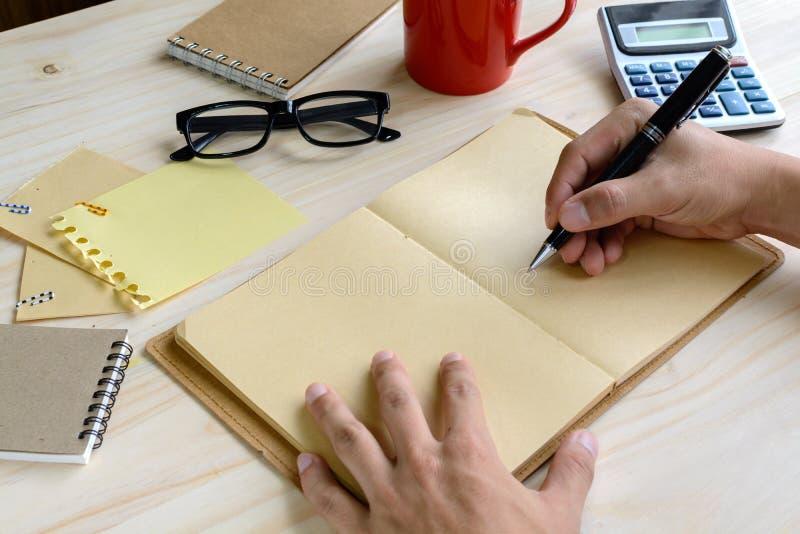 Carnet avec la tasse de café et de fourniture de bureau sur le bureau photos libres de droits