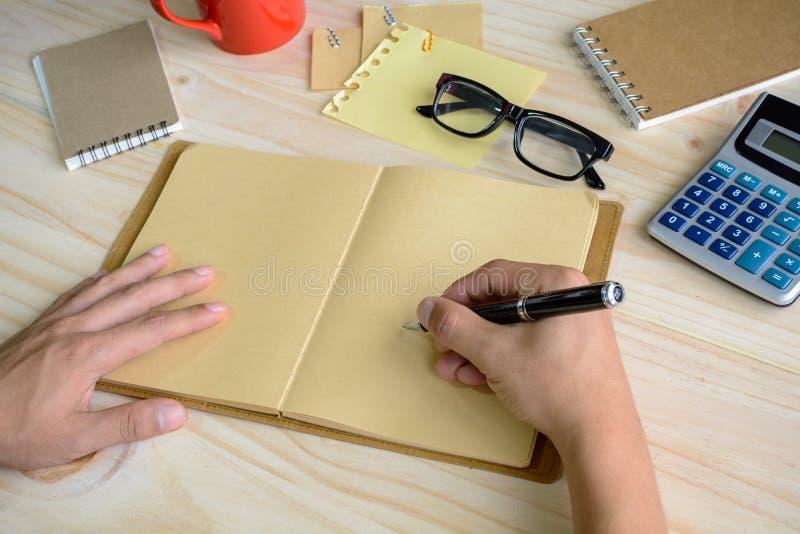 Carnet avec la tasse de café et de fourniture de bureau sur le bureau images libres de droits