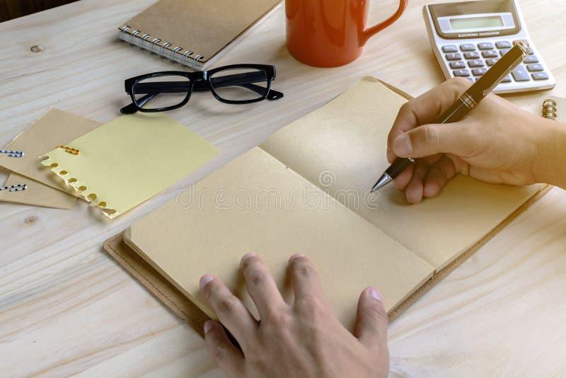 Carnet avec la tasse de café et de fourniture de bureau sur le bureau image stock