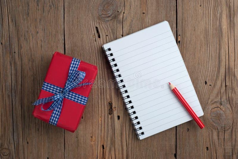 Carnet avec le cadeau et le crayon photographie stock