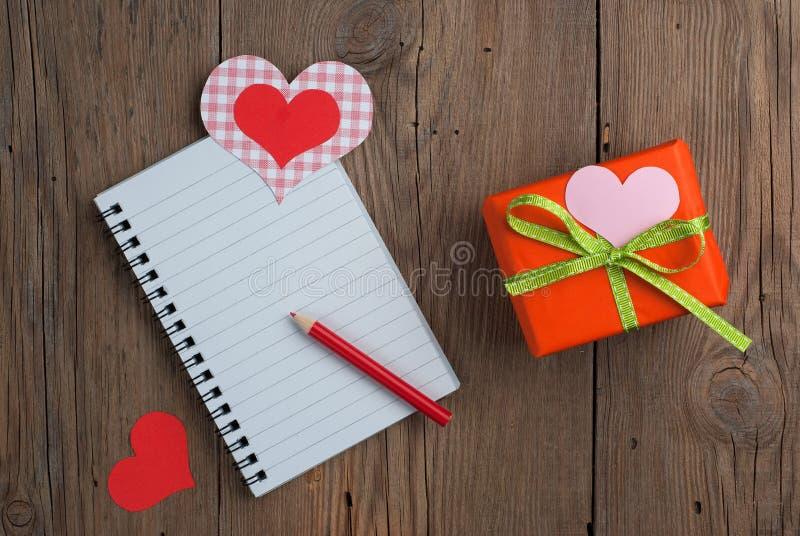 Carnet avec le cadeau, le crayon et les coeurs photo stock