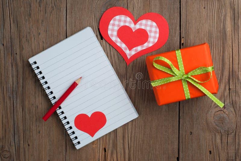 Carnet avec le cadeau, le crayon et les coeurs image libre de droits