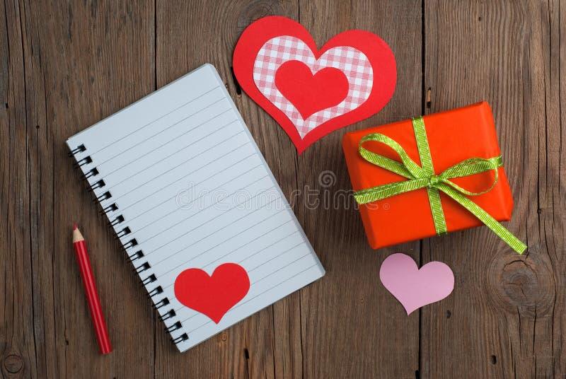 Carnet avec le cadeau, le crayon et les coeurs photographie stock libre de droits
