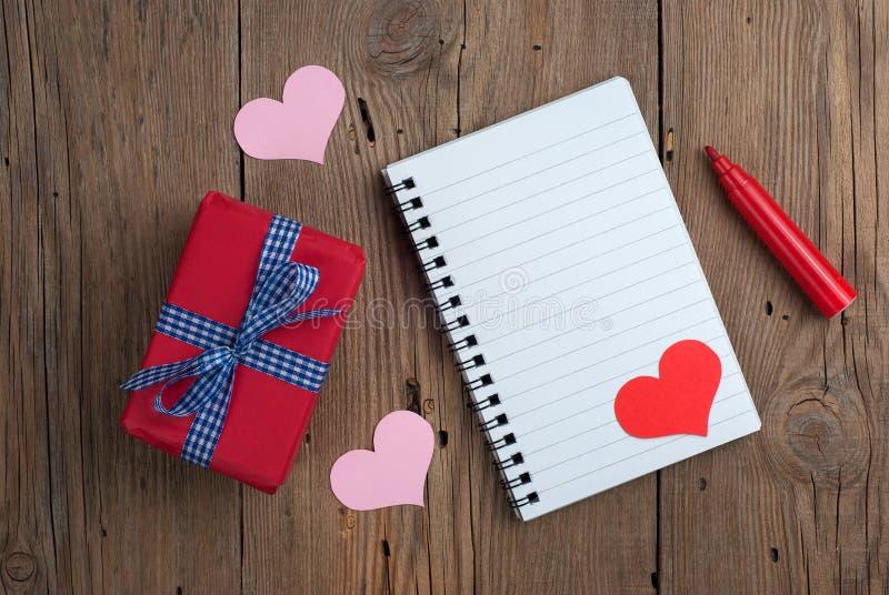 Carnet avec le cadeau, le stylo de feutre et les coeurs photographie stock libre de droits