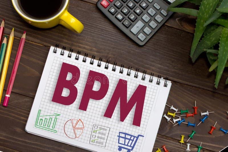 Carnet avec notes BPM sur la table de bureau avec des outils Concept avec des éléments d'infographics images stock