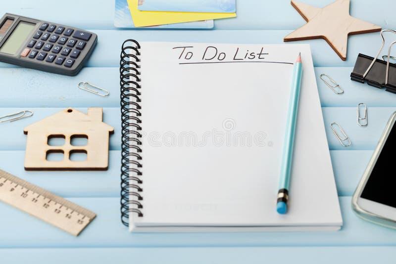 Carnet avec pour faire la liste et les différents outils de bureau sur le bureau rustique bleu photo stock