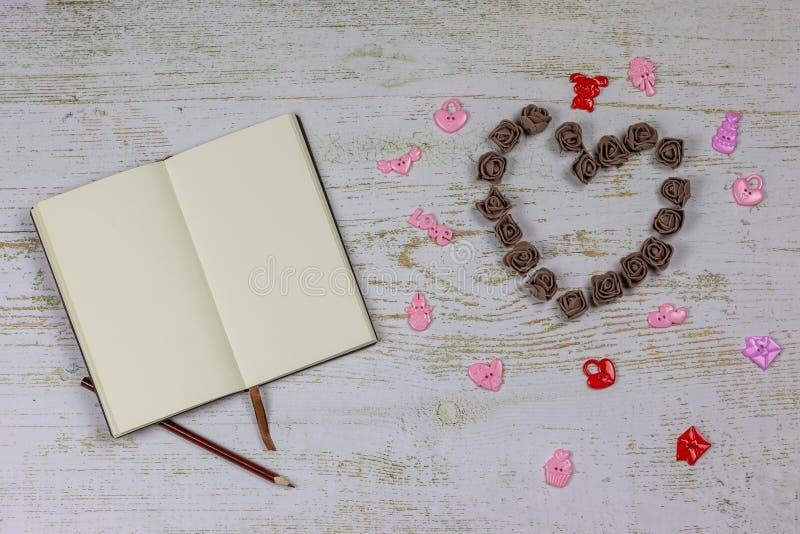 Carnet avec un crayon à côté d'un coeur fait de roses foncées avec des jouets Sur le fond en bois, photo ci-dessus Régal de l'amo image libre de droits