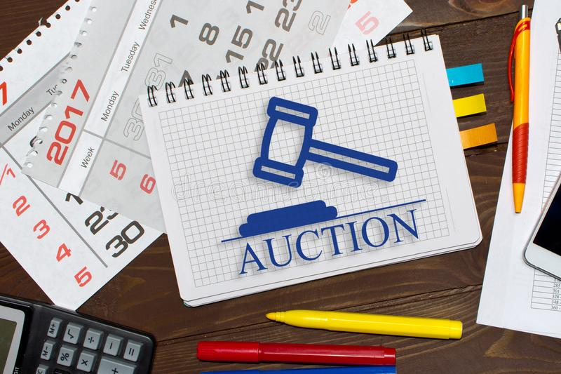 Carnet avec ventes aux enchères en ligne de notes sur la table de bureau avec des outils photographie stock libre de droits