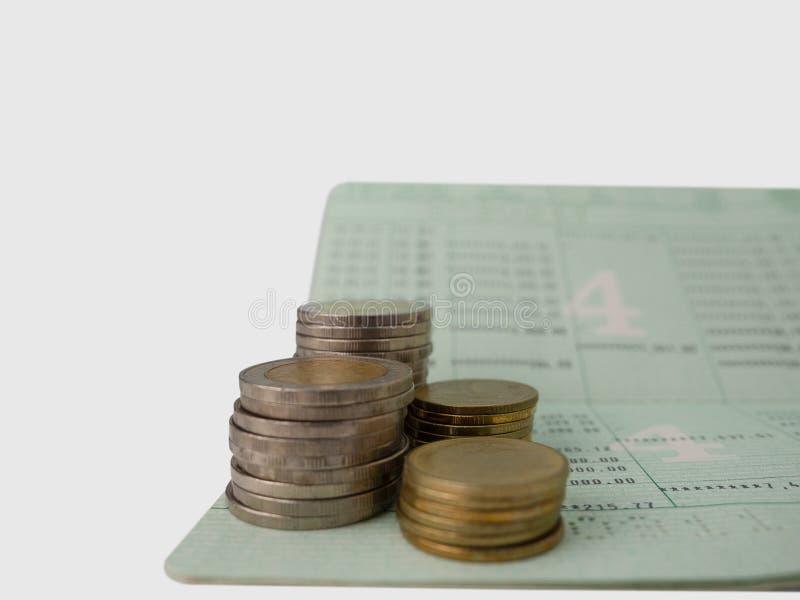 Carnet bancaire et piles des pièces de monnaie photographie stock