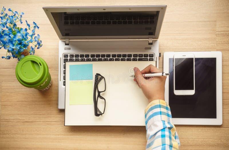 Carnet d'écriture de main sur un bureau fonctionnant image libre de droits