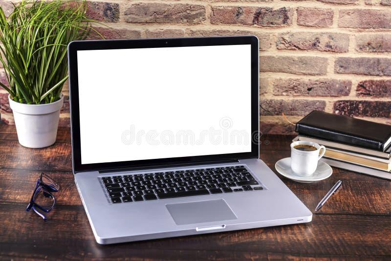 Carnet d'ordinateur portable avec l'écran vide et la tasse du stylo de café et de bloc-notes et les livres sur la table en bois photo libre de droits