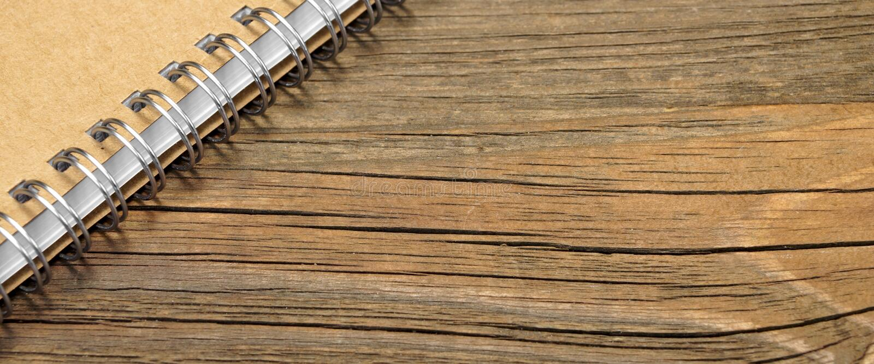 Carnet de notes à spirale avec la couverture de papier de Brown sur le Tableau rustique en bois images libres de droits