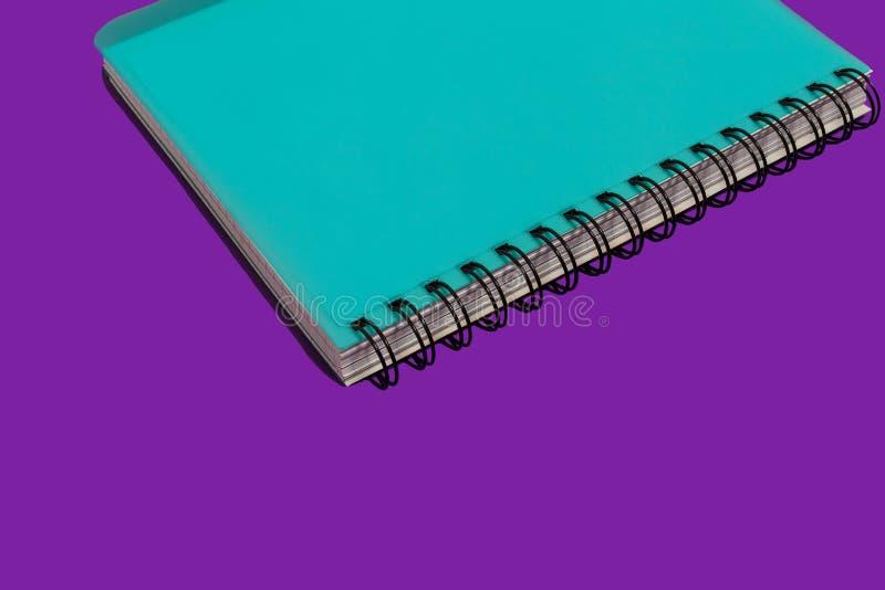 Carnet de notes ? spirale bleu sur un fond pourpre photo libre de droits