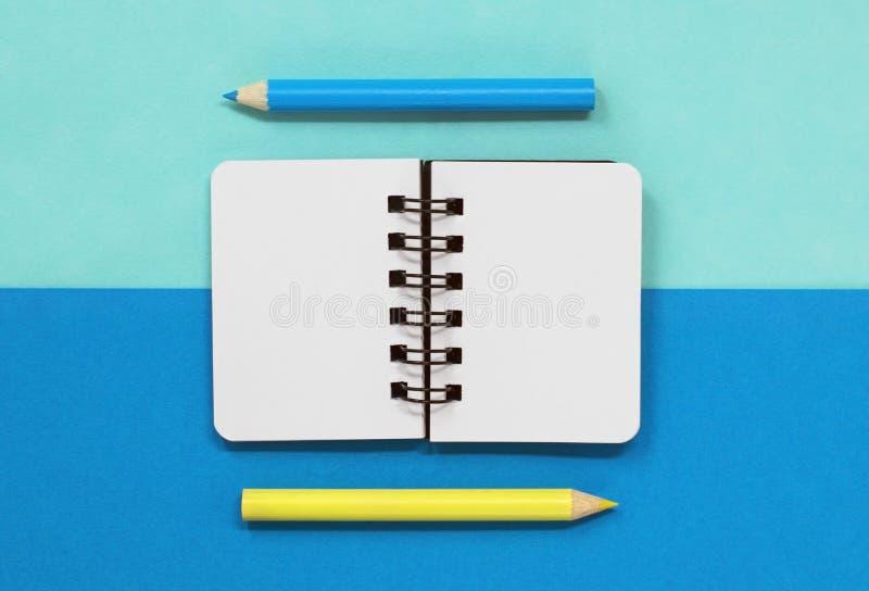 Carnet de notes à spirale ouvert avec les crayons bleus et jaunes, sur un fond bleu avec l'espace de copie image libre de droits