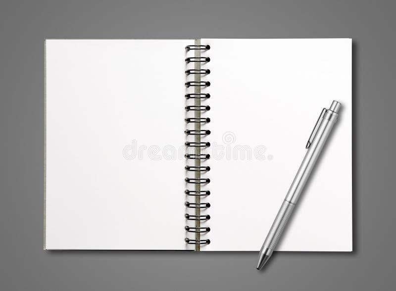 Carnet de notes à spirale ouvert et stylo de blanc d'isolement sur gris-foncé photographie stock