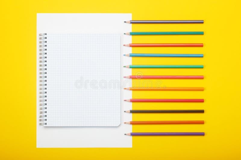 Carnet de notes et crayons de couleur sur fond jaune Imaginez un espace de copie pour vos idées photos stock
