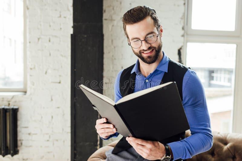 carnet de sourire à la mode de lecture d'homme d'affaires dans le grenier images libres de droits